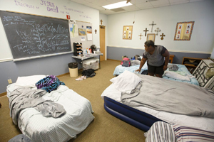 Image of Tamira Miller making her bed in a classroom where she and her children sleep