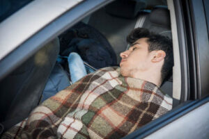 image of student sleeping in car